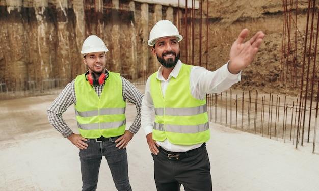新しい建物の基礎の上に立って、建設計画について話し合っているヘルメットとチョッキの楽観的な多様な男性の同僚