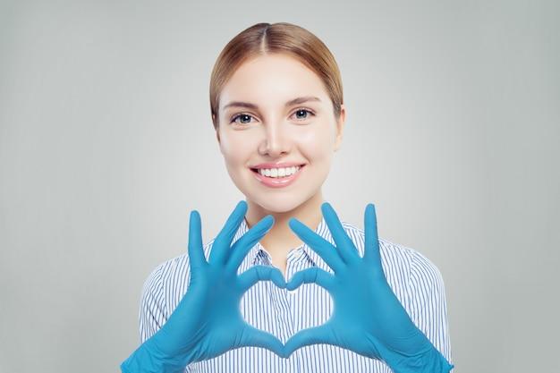 Оптимистичная женщина-врач делает сердце и улыбается.