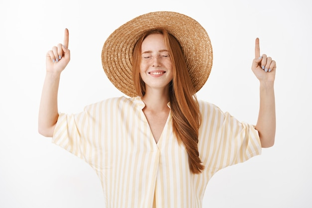 Optimistic dreamy and happy woman with red hair and freckles closing eyes with joyful look pointing up with raised hands wearing cute summer straw hat and striped yellow blouse