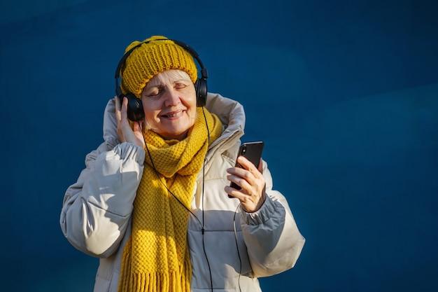 음악을 들으며 헤드폰을 끼고 웃고 있는 트렌디한 겉옷을 입은 낙관적인 노부인 프리미엄 사진