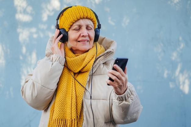 음악을 들으며 헤드폰을 끼고 웃고 있는 트렌디한 겉옷을 입은 낙관적인 노부인