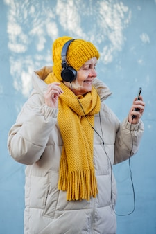 스마트폰으로 음악을 들으며 웃고 있는 트렌디한 겉옷을 입은 낙관적인 노부인