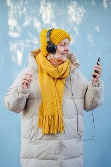 음악을 들으며 웃고 있는 트렌디한 겉옷을 입은 낙관적인 할머니