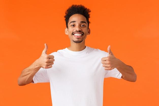 楽観的で熱狂的なアフリカ系アメリカ人の男性、白いtシャツ、完全に同意、幸せな気持ち