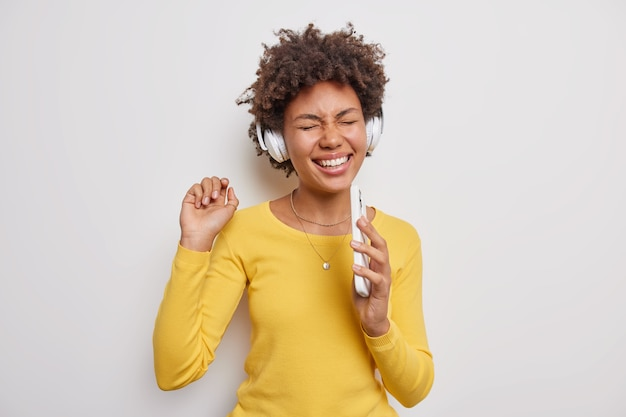 Optimistic ethnic female model with curly afro hair listens music in wireless headphones holds mobile phone sings favorite song dressed in casual yellow jumper on white