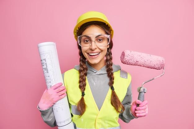 Оптимистичная опытная женщина-архитектор, занимающаяся ремонтом, держит малярный валик и свернутый чертеж с счастливым выражением лица, хвалится работодателем, носит строительную форму. положительный строитель
