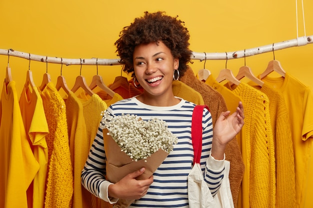 Optimistic female customer spends free time on shopping in store, poses with bouquet and bag against yellow clothes on racks, concentrated aside with broad smile