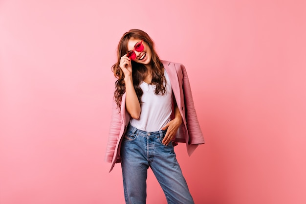 Optimistic ginger lady in bright sunglasses laughing. smiling stunning girl in jeans posing on pink.