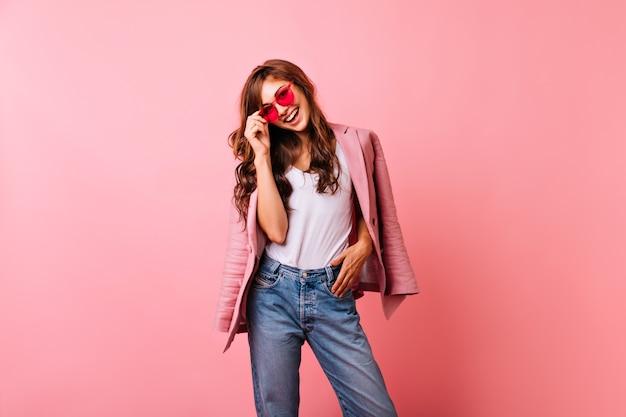 笑っている明るいサングラスの楽観的な生姜の女性。ピンクでポーズをとるジーンズの見事な女の子の笑顔。