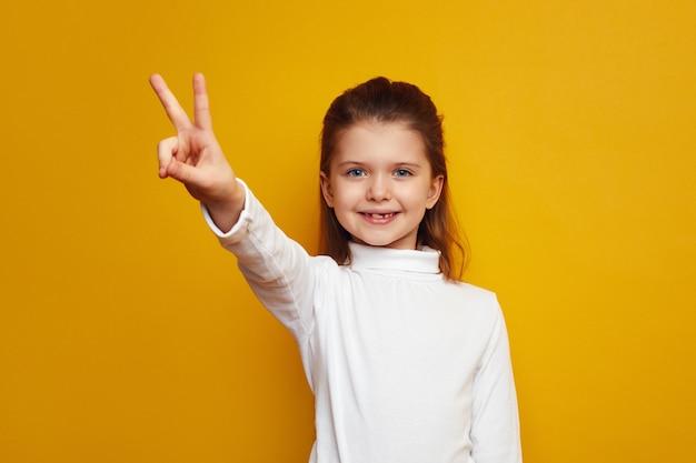 Оптимистичный ребенок-девочка показывает жест мира на ярко-желтом фоне