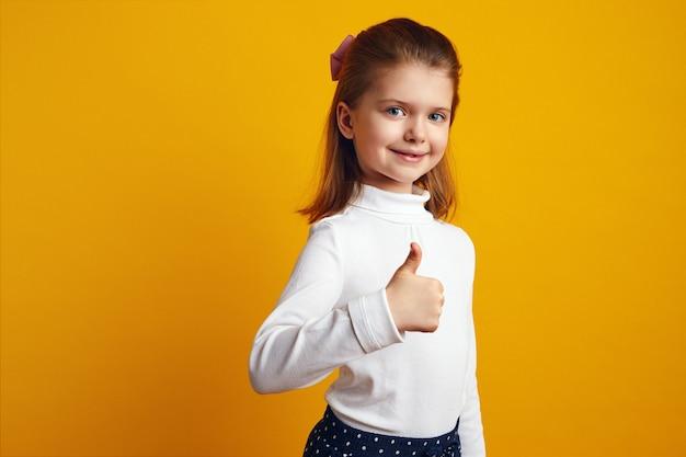 Оптимистичный ребенок девочка показывает палец вверх на ярко-желтом фоне