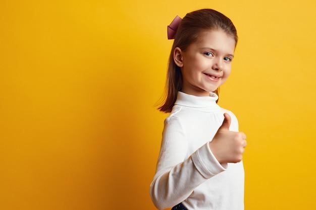 밝은 노란색 벽에 엄지 손가락을 보여주는 낙관적 여자 아이