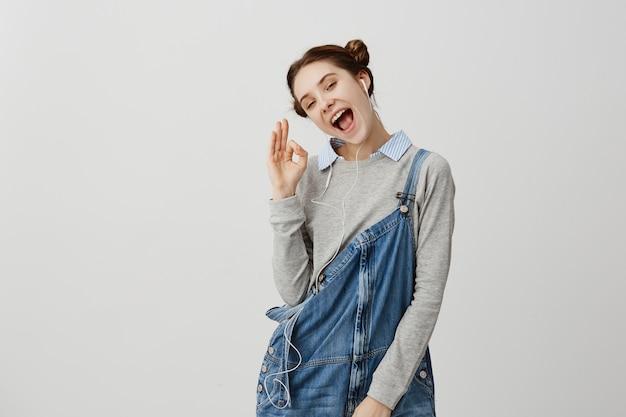 音に満足している現代の電子デバイスを使用して二重パンで髪の楽観的な女の子。新しいイヤホンを愛するように快活な兆しを見せている快活な女性。人間の感情