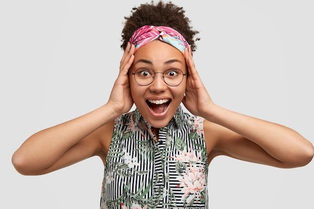 楽観的な嬉しい女性は喜びから頭に手を保ちます