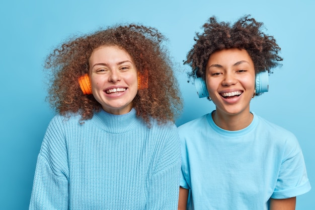 Optimistic good looking two women with curly hair smile broadly have fun while listen music via headphones enjoy favorite track dressed casually isolated over blue wall. lifestyle concept