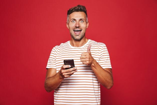 赤で隔離の携帯電話を笑顔で保持している縞模様のtシャツの楽観的な男30代