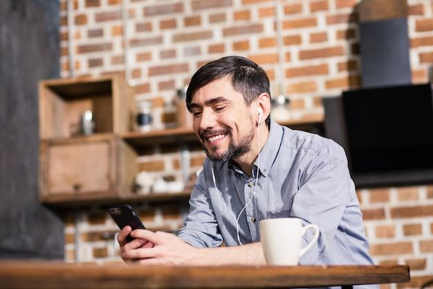 Оптимистичный красивый мужчина улыбается, используя смартфон и сидя на кухне
