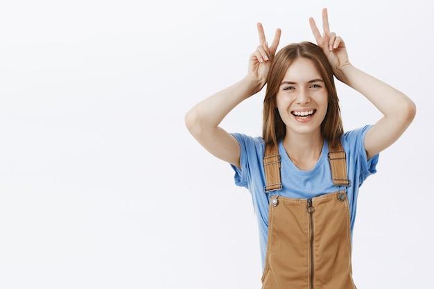 Оптимистичная счастливая привлекательная девушка показывает жест мира и смеется