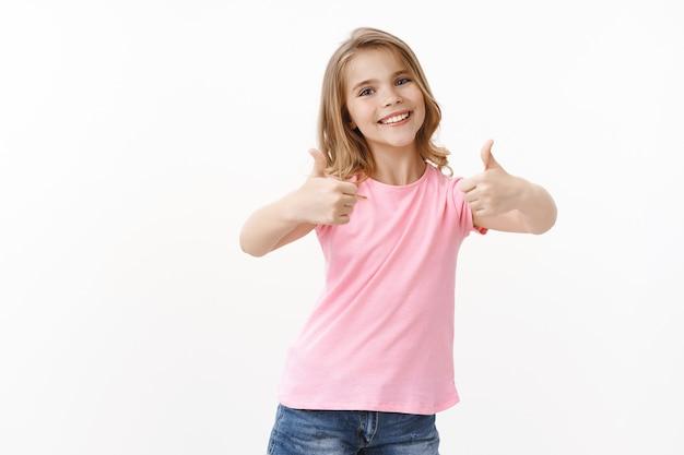 Оптимистичная счастливая жизнерадостная молодая белокурая девочка, дочь благодарит папу за отличный потрясающий подарок, показывает одобрение и нравится жест, радостно улыбается, принимает крутой подарок, стоит у белой стены