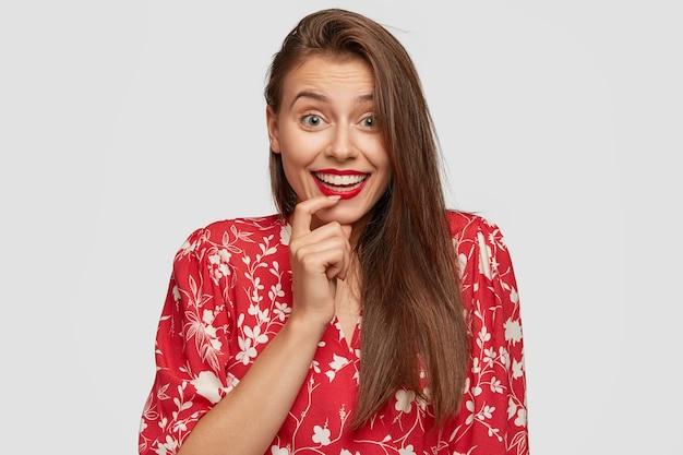 楽観的な幸せなヨーロッパの女性は赤い口紅を着て、楽しく見えます