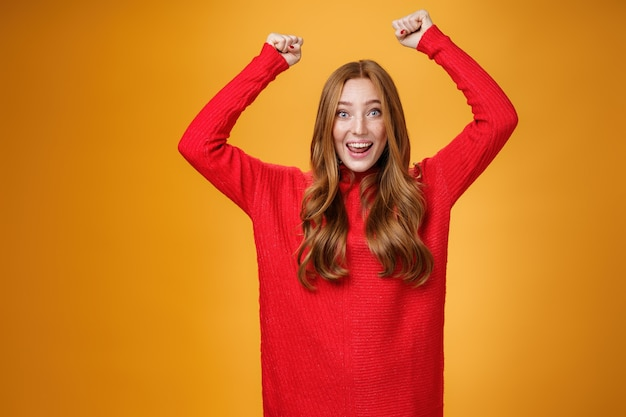 Optimistic happy and supportive ginger girl yelling cheering words, raising hands joyfully and smiling broadly triumphing, celebrating success and win, posing satisfied and excited against orange wall