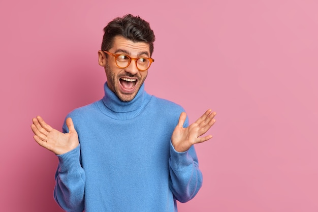 Optimistic hipster guy raises palms and reacts on awesome news