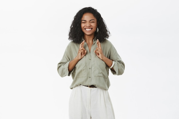 Optimistic hopeful good-looking happy and excited african american young new office worker in trendy outfit