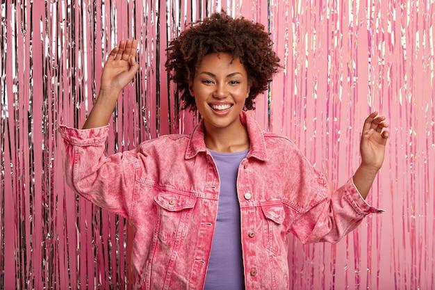 La signora ottimista alza le mani, balla al ritmo della musica alla festa, indossa una giacca di jeans casual rosa, posa su un photozone decorato con orpelli