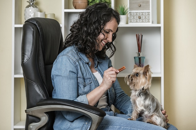 Оптимистичная дама тренирует собаку на стуле