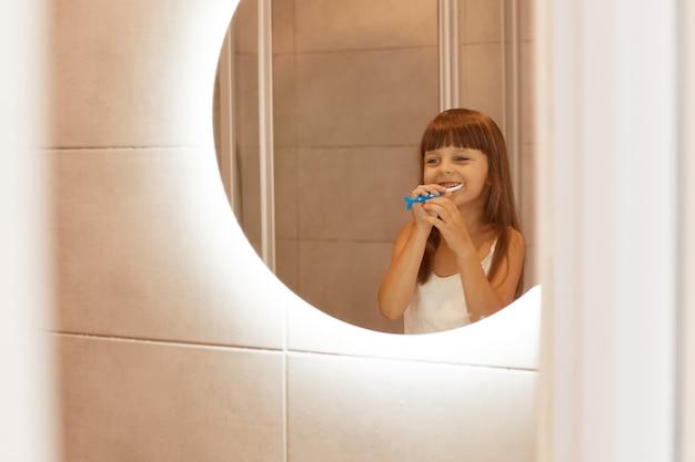 Оптимистичный маленький ребенок женского пола чистит зубы в ванной, стоит перед зеркалом и счастливо улыбается, одетый в белую повседневную футболку без рукавов.