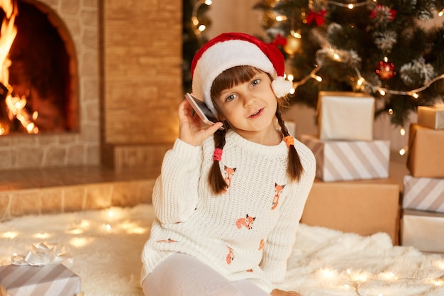 Optimistic little girl wearing white sweater and santa claus hat, looking at camera, having festive mood, taking via phone, sitting on floor near christmas tree, present boxes and fireplace.