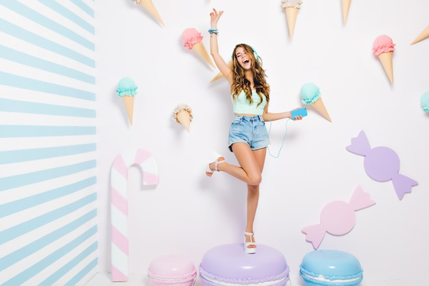 Optimistic long-haired girl standing on one leg enjoying music and singing, holding phone in hand. full-length portrait of pleased young woman posing on purple macaroon in front of decorated wall.