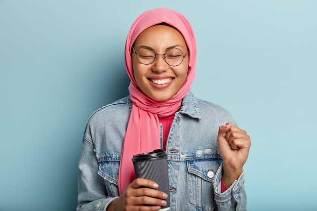 Optimistic lovely muslim woman clenches fist, closes eyes from pleasure