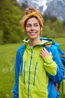 Viaggiatore adorabile ottimista con espressione felice, indossa una giacca a vento blu e verde, porta lo zaino