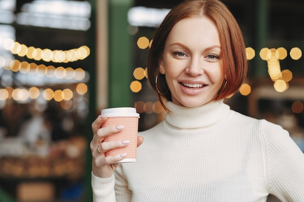 Optimistic lovely woman with dyed hair, satisfied expression, wears turtleneck jumper