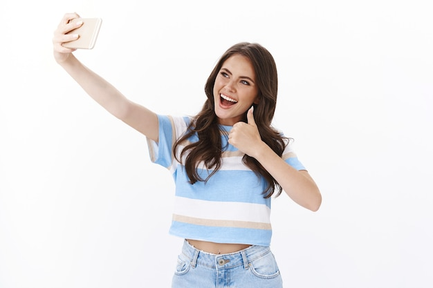 Optimistic lucky cute female feeling happy, travel around world taking selfies, extend arm with smartphone joyfully smiling, pose near beautiful sightseeing show thumb up approval gesture