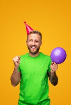 Оптимистичный мужчина с воздушным шаром празднует день рождения