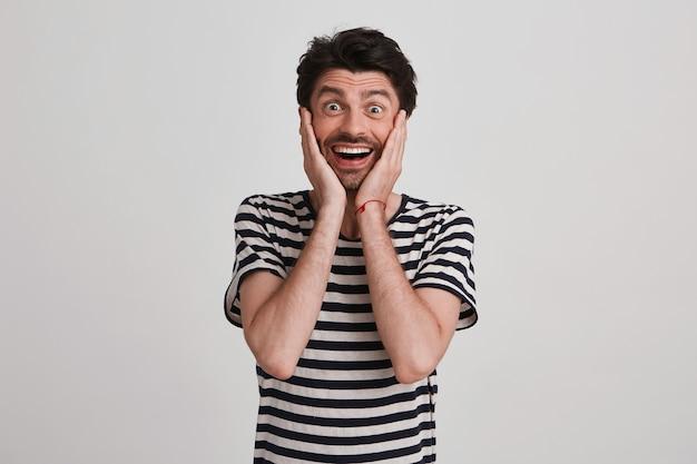 Maschio ottimista con un'espressione felice, tiene le mani sulle guance, si sente scosso e felice, isolato sul muro bianco