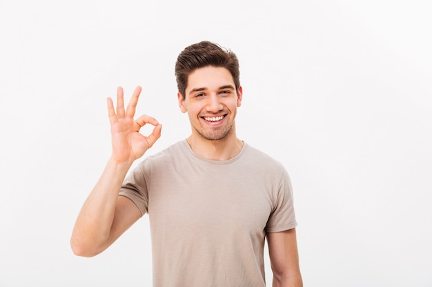 Optimistic man having bristle and brown hair showing ok sign on camera with sincere look, isolated over white wall