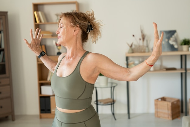 회색 탄성 운동복을 입은 낙관적 인 중년 여성이 거실에서 운동을하고 집에서 항상 대출을합니다.