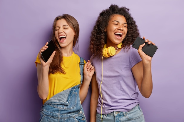 Optimistic pleased mixed race women sing favourite song in smart phones, have fun and enjoy music, keep eyes shut, move actively