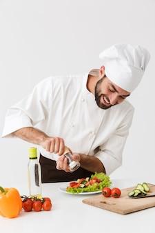 楽観的で、新鮮な野菜を使った均一な料理で前向きな幸せな若いシェフを喜ばせました。