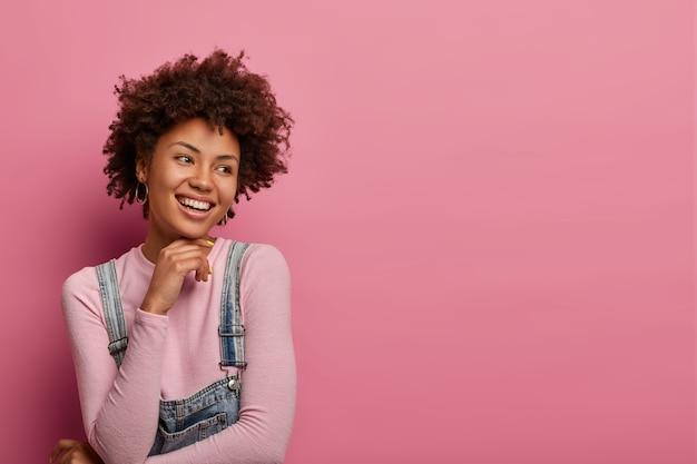 낙관적 인 유쾌한 여성 모델은 밝은 미소로 옆으로 보이고, 옆으로 집중되어 있으며, 관능적 인 표현을 가지고 있으며, 그녀의 선택을 행복하게하고, 만족을 표현하고, 장미 빛 벽 위에 모델을 표현합니다.