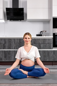 Optimistic pregnant lady sit on floor with crossed legs smiling namaste