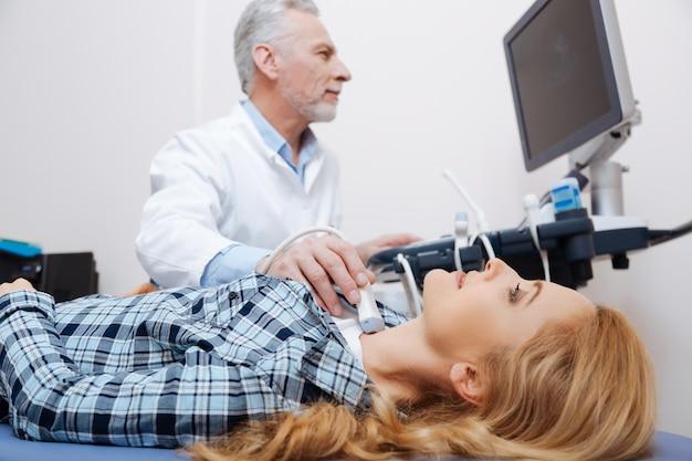 医療従事者が超音波頸部血管のモニタリングを提供している間、医者を訪問し、医療用ソファに横になっている楽観的なかなり動かない女性