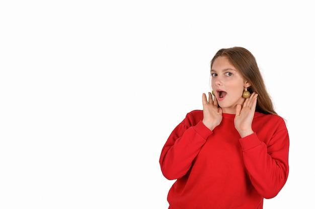 Оптимистичная красивая женщина в повседневном красном свитере с изолированными елочными шарами