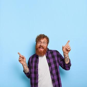 Оптимистичный рыжеволосый бородатый парень радостно показывает в разные стороны