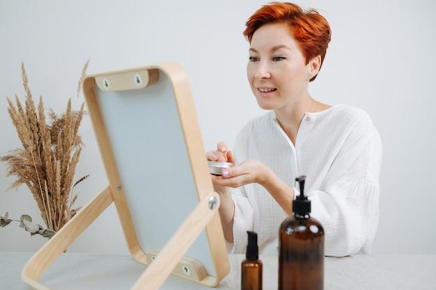 Оптимистичная коротковолосая женщина смотрит в зеркало в деревянной раме, нанося консилер. использование экологически чистых продуктов и вещей. она наслаждается результатами.