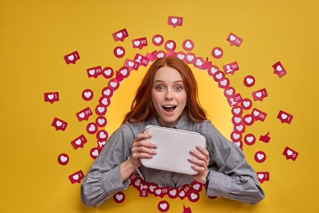 インターネットで人々の反応を待っている、新しい財布を見せている楽観的な笑顔の女性ブロガー。