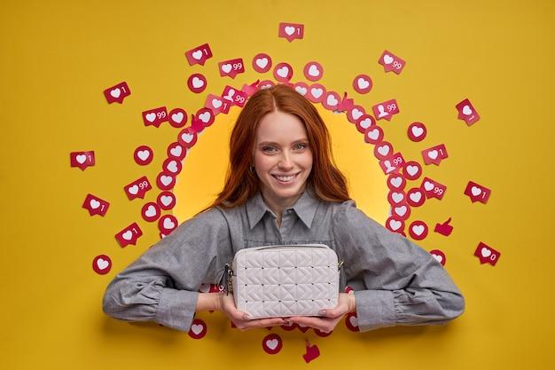 Оптимистичная улыбающаяся женщина-блогер показывает новую сумочку, ожидая реакции людей